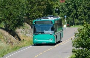 Green bus driving through an area with lush vegetation